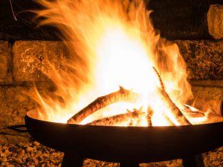 Feuerschale bei Nacht vor einer Steinmauer