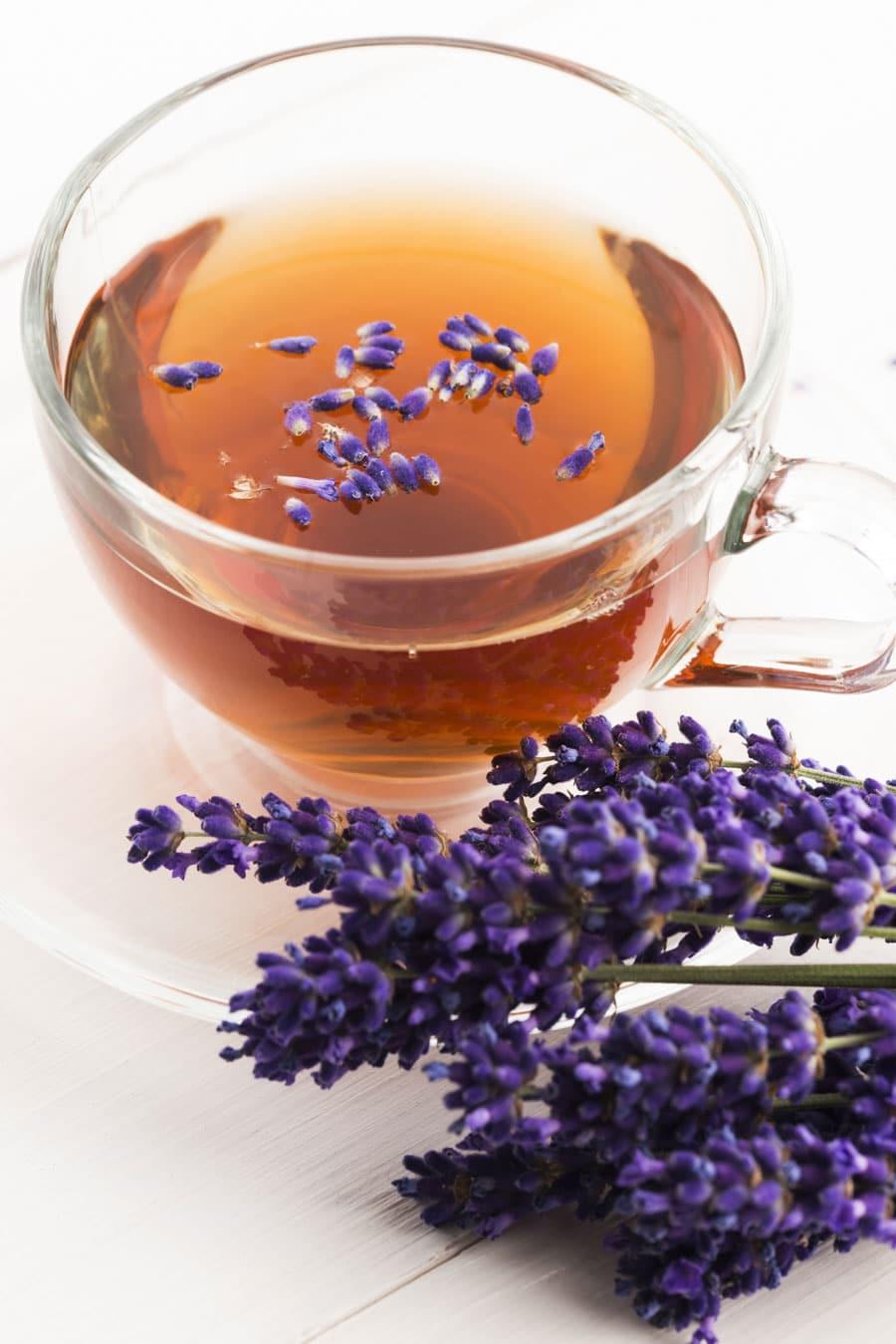 Lavendelblüten neben einer Glastasse mit Lavendeltee