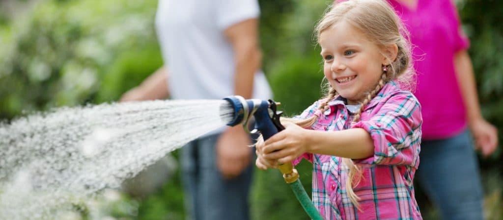 Kind mit Gartenschlauch wässert den Garten