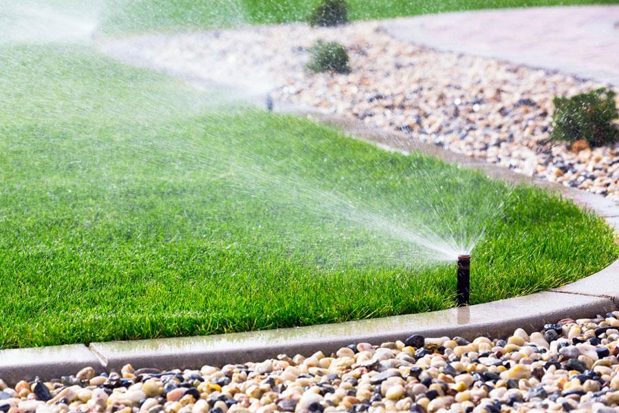 Gartensprenger - Versenkregner am Gartenrand bewässert den Rasen