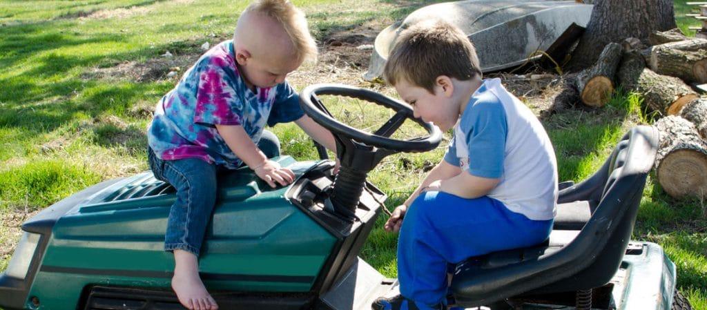 Zwei Kinder sitzen auf einem Aufsitzmäher